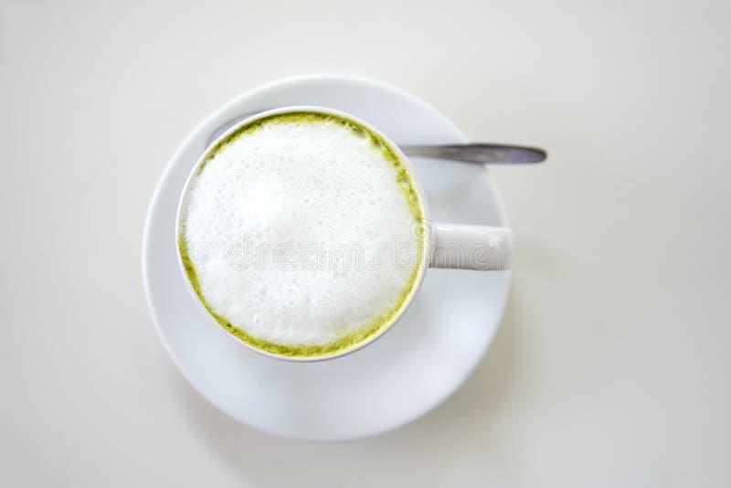 Den bästa sikten av mjölkar matchalatte för grönt te med tefatet på vit tabellbakgrund Varmt mjölka gräsplante (selektiv fokus) i arkivfoto