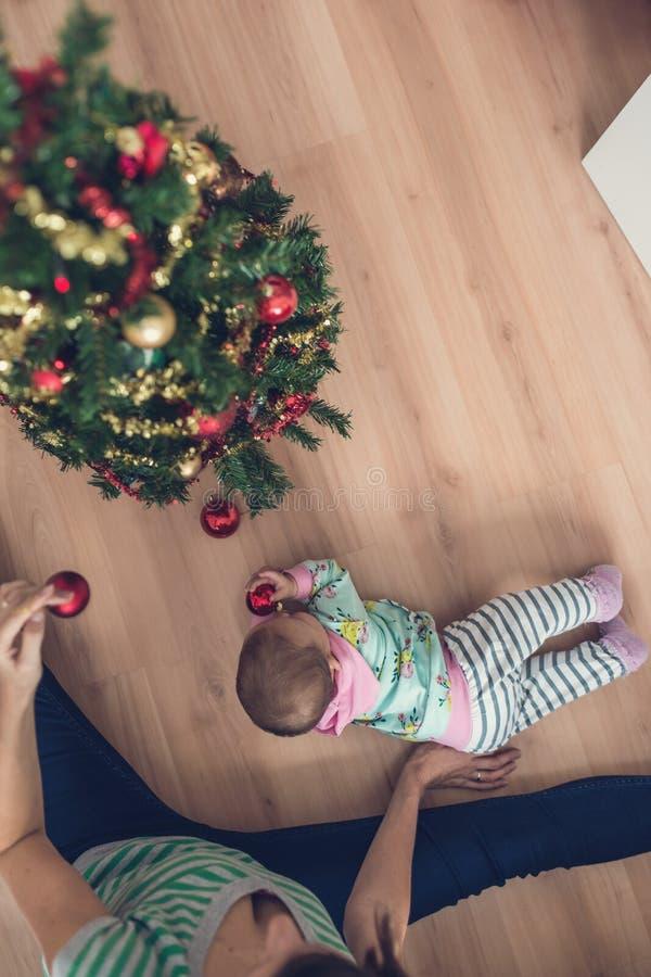 Den bästa sikten av modern som dekorerar julgranen med, behandla som ett barn dottern arkivfoto