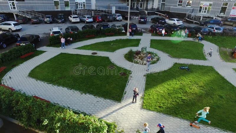Den bästa sikten av nätta små barn kör på grönt gräs, ler och ser kameran gem Barn i parkera royaltyfria bilder