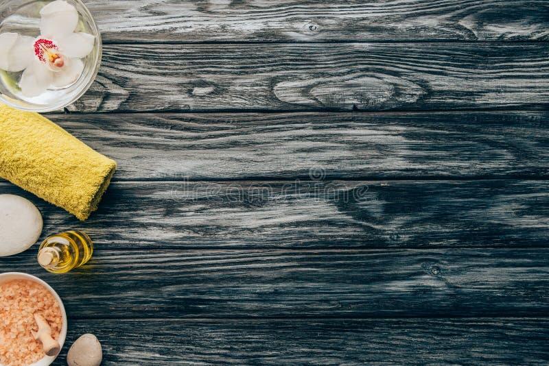 den bästa sikten av den ordnade handduken, nödvändig olja, saltar och orkidéblomma i bunken för massage och brunnsort arkivfoto