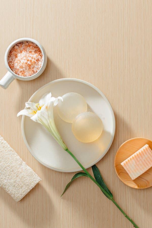 Den bästa sikten av organiska brunnsortskincareprodukter med saltar, blommor, naturlig tvål, handdukar och polermedelstenen arkivfoton