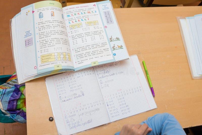 Den bästa sikten av partiet, som studenten sitter för på skrivbordet, lägger en lärobok och en anteckningsbok arkivfoton