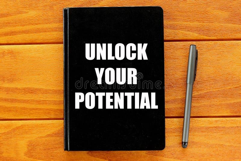 Den bästa sikten av pennan och anteckningsboken som är skriftlig med, låser din spänning på träbakgrund upp äganderätt för home t arkivbild