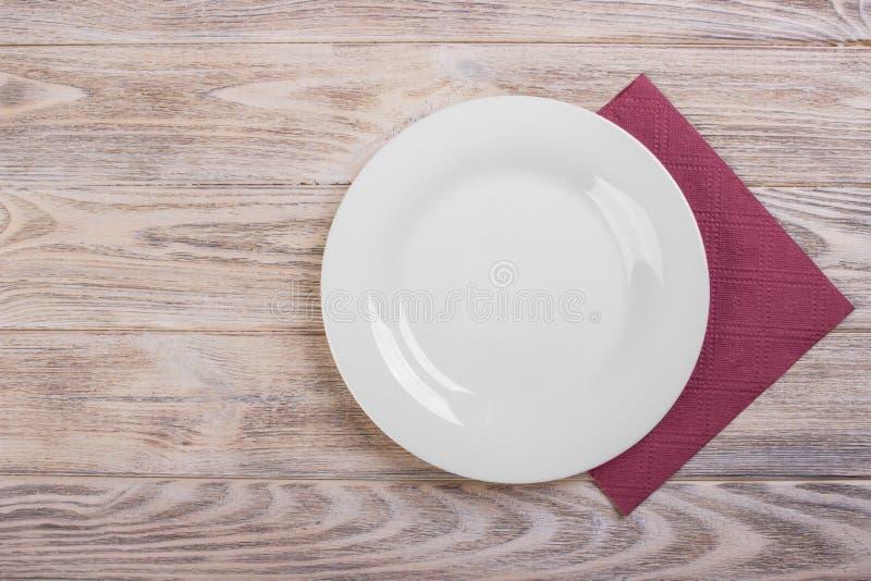 Den bästa sikten av rent tömmer plattan på trätabletopen med servetten arkivfoton