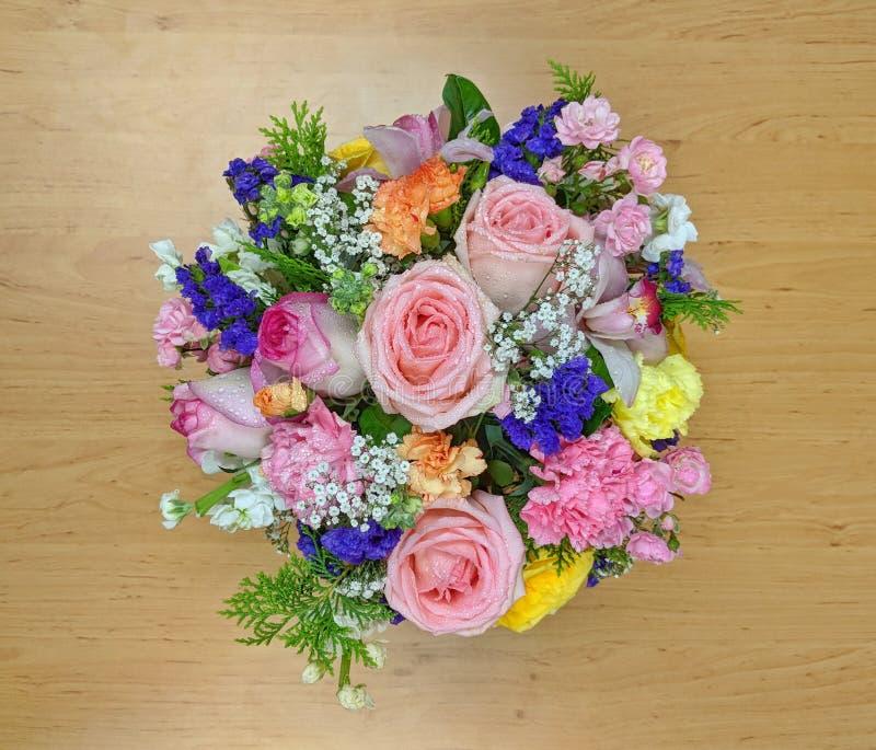 Den bästa sikten av rosa färger blommar buketten på ett träbräde royaltyfri foto