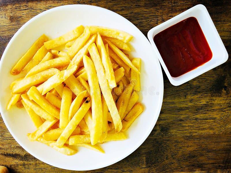 Den bästa sikten av smakliga den fransmansmåfiskar eller potatisen steker med ketchup på trätabellen arkivfoton