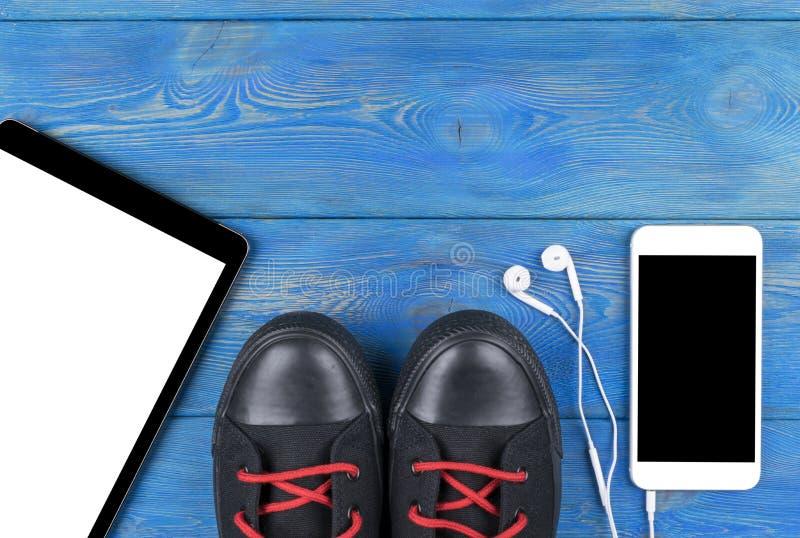 Den bästa sikten av sportskor vid minnestavladatoren och mobiltelefonen med skärm- och i-örat hörlurar och vitt tömmer mellanrume royaltyfria foton