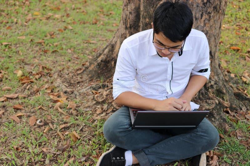 Den bästa sikten av den stiliga asiatiska unga mannen som arbetar mot bärbar datordatoren i utomhus-, parkerar royaltyfria bilder