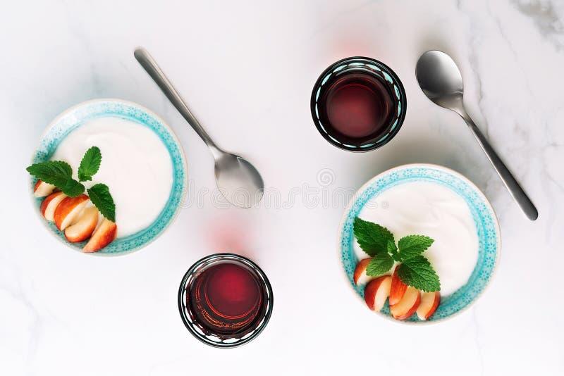 Den bästa sikten av den sunda frukosten av naturlig grekisk yoghurt, frukt och fruktsaft på marmorerar tabellen Lekmanna- l?genhe royaltyfri bild