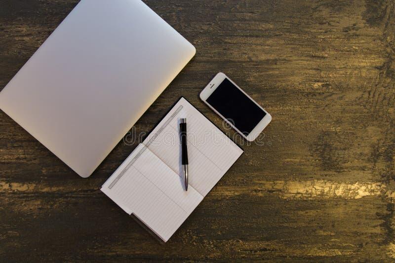 Den bästa sikten av tabellen eller skrivbordet med bärbara datorn, den tomma anteckningsboken, penna och ilar telefonen på gammal royaltyfria foton