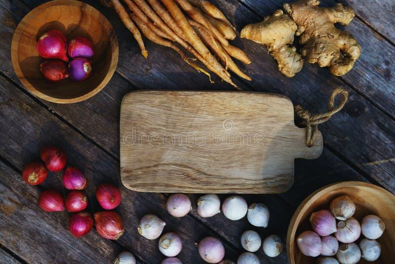 Den bästa sikten av trätabellen mycket av växt- grönsakingredienser, vitlök, den röda löken, finger rotar, ingefäran, kopieringsu fotografering för bildbyråer