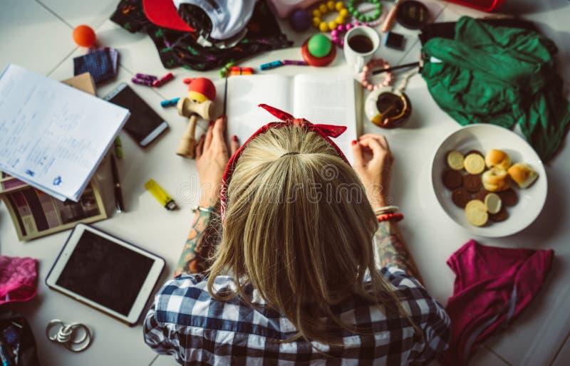 Den bästa sikten av den unga blonda kvinnan i en bandana läste en bok som ligger på golvet Röran i rummet modern deltagare royaltyfria foton