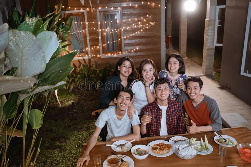Den bästa sikten av ungt asiatiskt folk tycker om deras matställe i hem- trädgård med vännen arkivbild