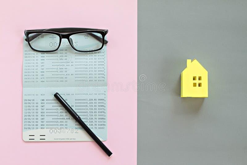 Den bästa sikten eller lägenheten lägger av sparkontobankbok och gul pappers- husmodell på bakgrund arkivbilder