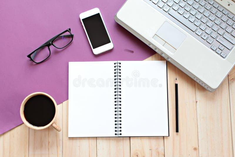 Den bästa sikten eller lägenheten lägger av utrymme för arbete för kontorstabellskrivbord med den tomma anteckningsboken, den sma royaltyfria foton