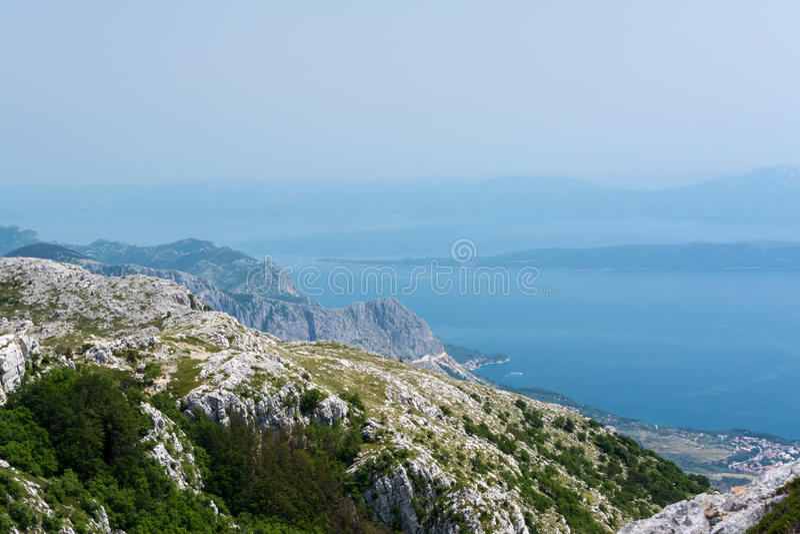 Den bästa sikten på blått fördunklade havsfjärden från bergklipporna av den Biokovo nationalparken nära den Makarska semesterorte royaltyfri bild