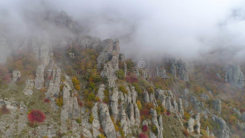 Den bästa sikten på lättnad av vaggar höst i dimma skjutit Sikten av vaggar bildande av berget med kulört torrt gräs och buskar royaltyfria foton