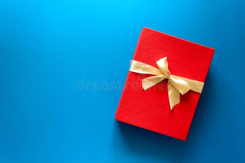 Den bästa sikten på den röda julgåvaasken dekorerade med bandet på bakgrund för blått papper arkivfoto