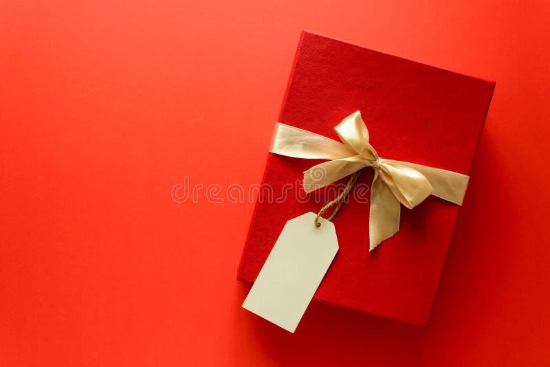 Den bästa sikten på den röda julgåvaasken dekorerade med bandet på röd pappers- bakgrund Nytt år, ferier och berömgarneringar c royaltyfri foto