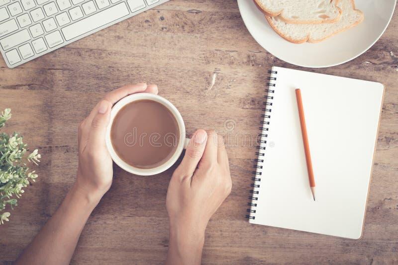 Den b?sta sikten av aff?rshanden p? skrivbordet har p? kaffe, rostat br?d, anteckningsbokmellanrumet och blyertspennan royaltyfria bilder