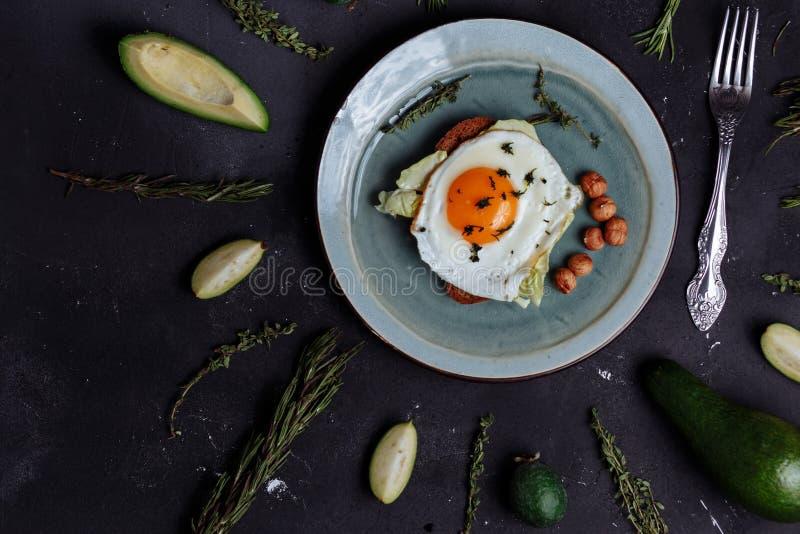 Den b?sta sikten av den sunda frukosten f?rvanskade ?gg med br?d och muttrar i en platta p? svart bakgrund med avokadot, rosmarin arkivfoto