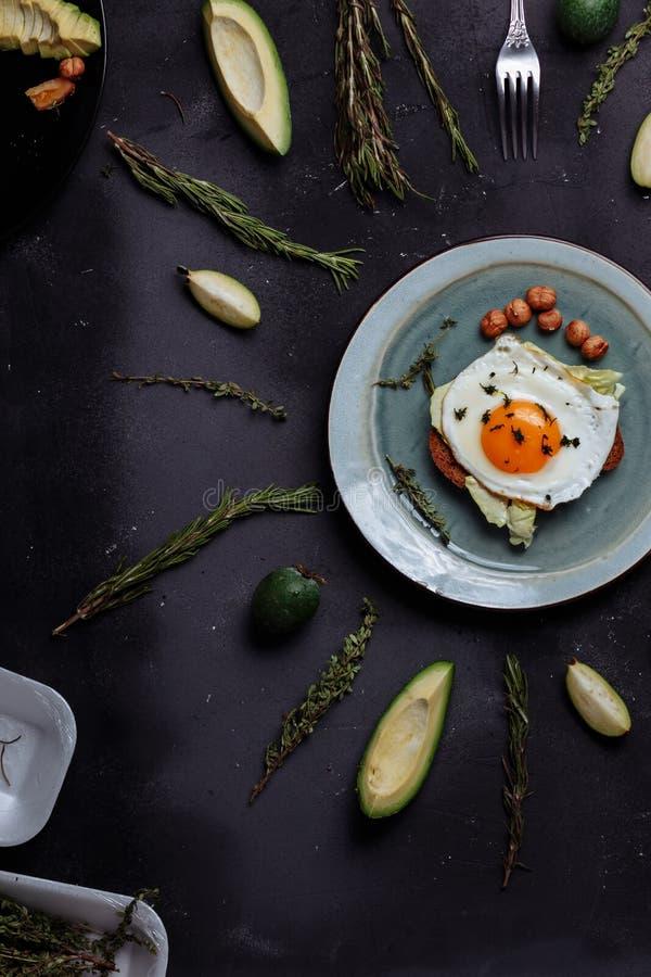 Den b?sta sikten av den sunda frukosten f?rvanskade ?gg med br?d och muttrar i en platta p? svart bakgrund med avokadot, rosmarin royaltyfria bilder
