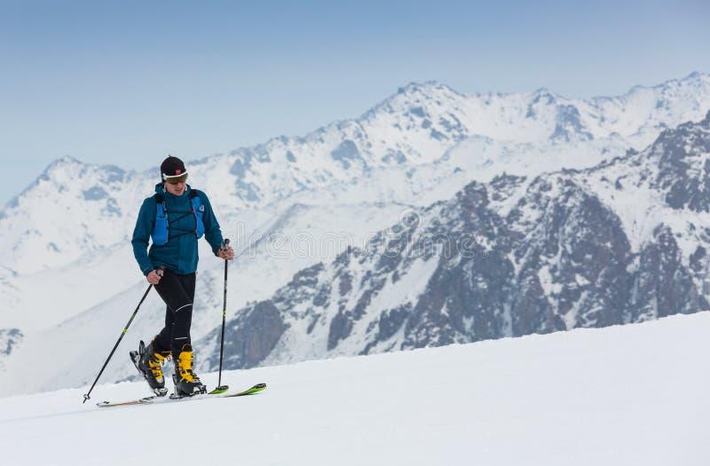 Den backcountry bergsbestigaren skidar gå upp längs en snöig kant med skidar i ryggsäcken I blå himmel för bakgrund och skinande fotografering för bildbyråer