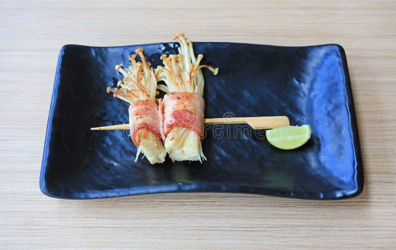 Den bacon- och Enoki champinjonrullpinnen tjänade som med citronen på den svarta plattan på trätabellen Japansk kokkonstmat royaltyfri foto