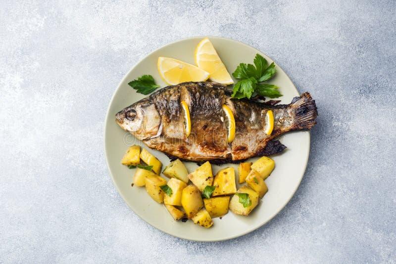 Den bakade fisken kverulerar med citrongräsplaner och potatisar på en platta kopiera avstånd royaltyfri fotografi