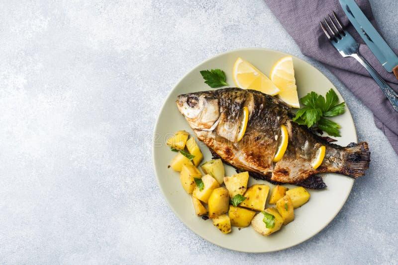Den bakade fisken kverulerar med citrongräsplaner och potatisar på en platta kopiera avstånd royaltyfria foton