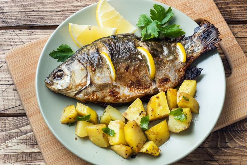 Den bakade fisken kverulerar med citrongräsplaner och potatisar på en platta spelrum med lampa arkivfoton
