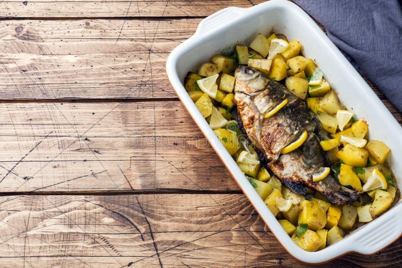 Den bakade fisken kverulerar med potatisar i en keramisk panna Lantlig stil kopiera avstånd royaltyfri bild