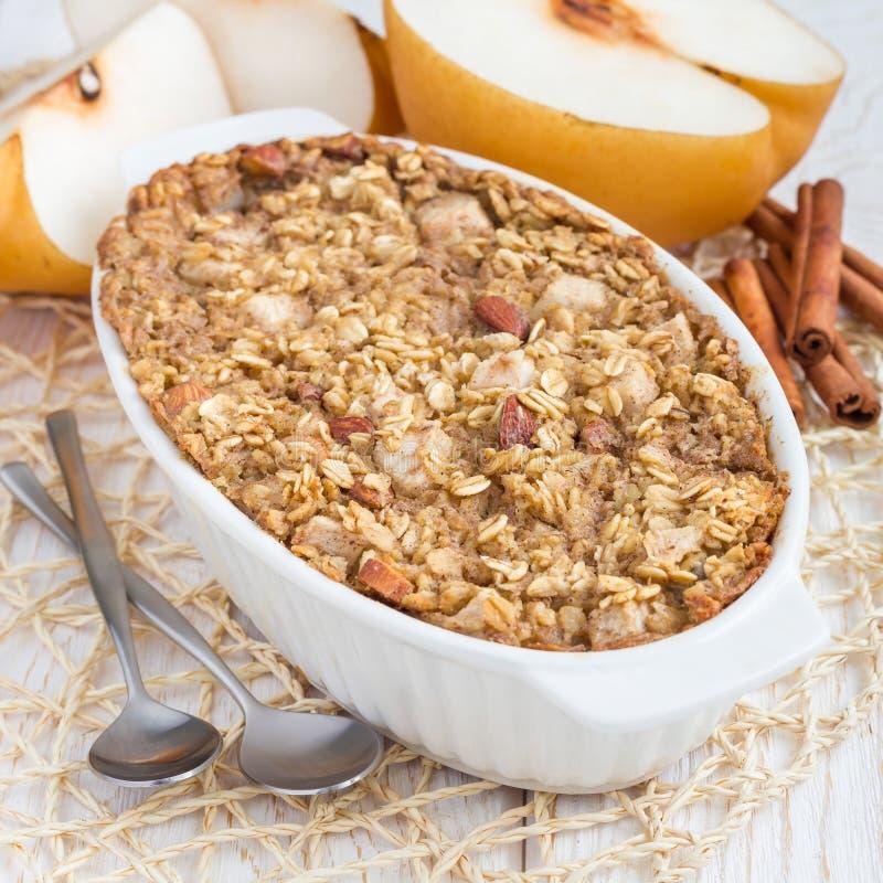Den bakade havremjölet med muttrar, mandel mjölkar, honung, kryddor och det asiatiska päronet, fyrkant arkivfoto