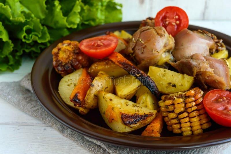 Den bakade potatisen med stycken grillar gåsen, grönsaker och havregallret royaltyfri bild