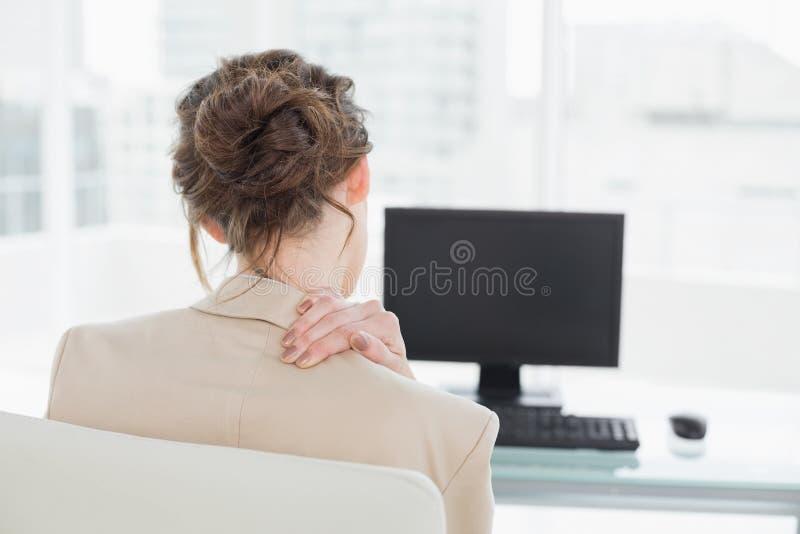 Den bakre sikten av affärskvinnan med halsen smärtar i regeringsställning royaltyfri fotografi