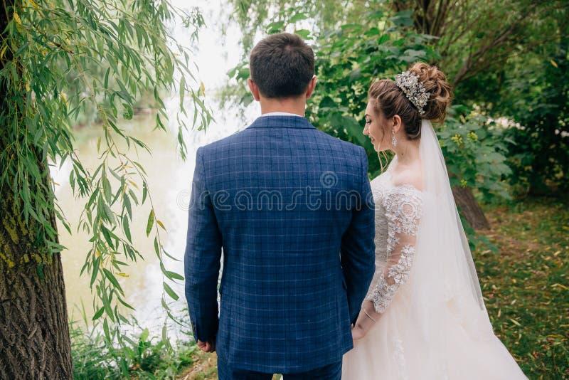 Den bakre sikten av bruden och brudgummen på deras bröllopdag avgjorde att ta en gå i en härlig gräsplan parkerar Nygifta persone royaltyfri fotografi