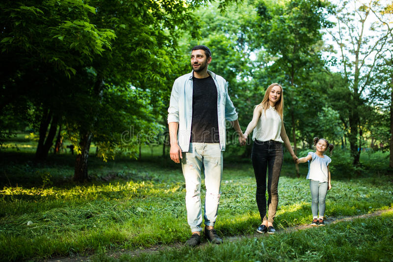 Den bakre sikten av den unga familjen som går i sommar, parkerar royaltyfria foton