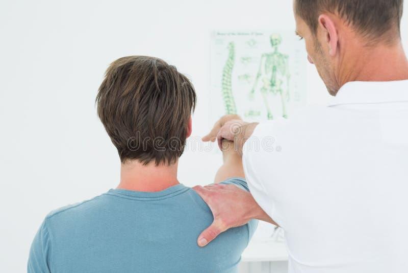 Den bakre sikten av en fysioterapeut som sträcker a, mans armen royaltyfri bild