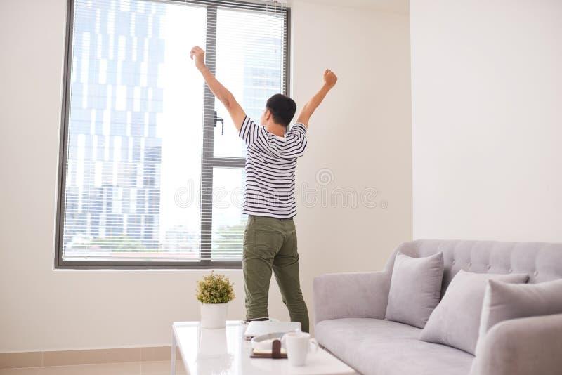Den bakre sikten av en ung Asien man som sträcker hans armar, near fönstret på royaltyfria foton