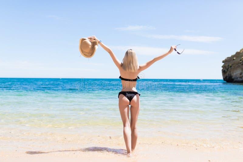 Den bakre sikten av den härliga unga kvinnan lyftte hennes händer på stranden royaltyfria foton