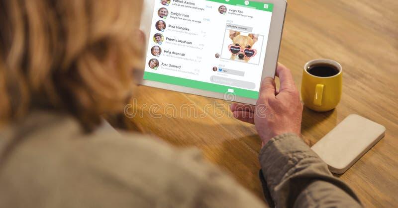 Den bakre sikten av mannen som använder den digitala minnestavlan med socialt massmedia, har kontakt på skärmen fotografering för bildbyråer
