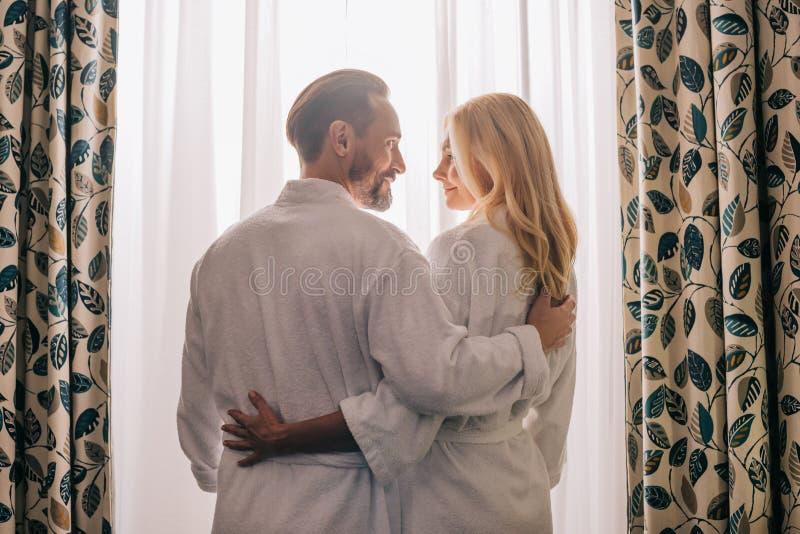 den bakre sikten av mitt åldrades förälskade bärande badrockar för par och att le sig i hotell arkivfoto