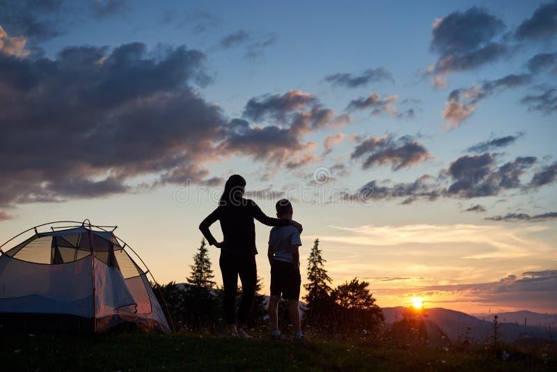Den bakre sikten av modern kramar hennes son nära tältet överst av berget som tycker om sikt av solen fotografering för bildbyråer