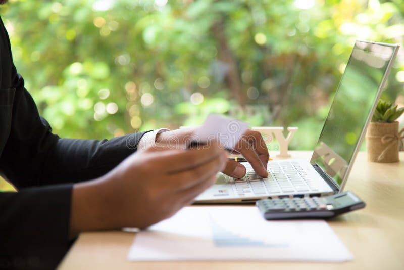Den bakre sikten av den moderna affärsmannen räcker hållande kreditkortmaskinskrivningnummer på datortangentbordet, medan sitta m royaltyfri foto