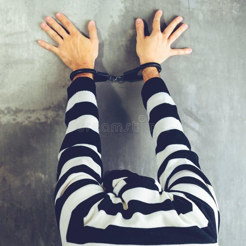 Den bakre sikten av den oidentifierade fången i fängelse rev av likformigst arkivbild