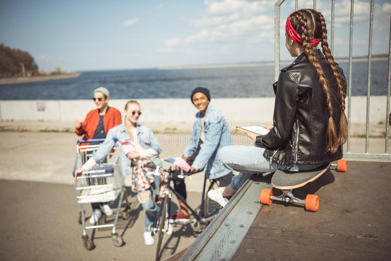 Den bakre sikten av tonåringflickan som använder den digitala minnestavlan och sitter på skateboarden i skateboard, parkerar arkivfoton