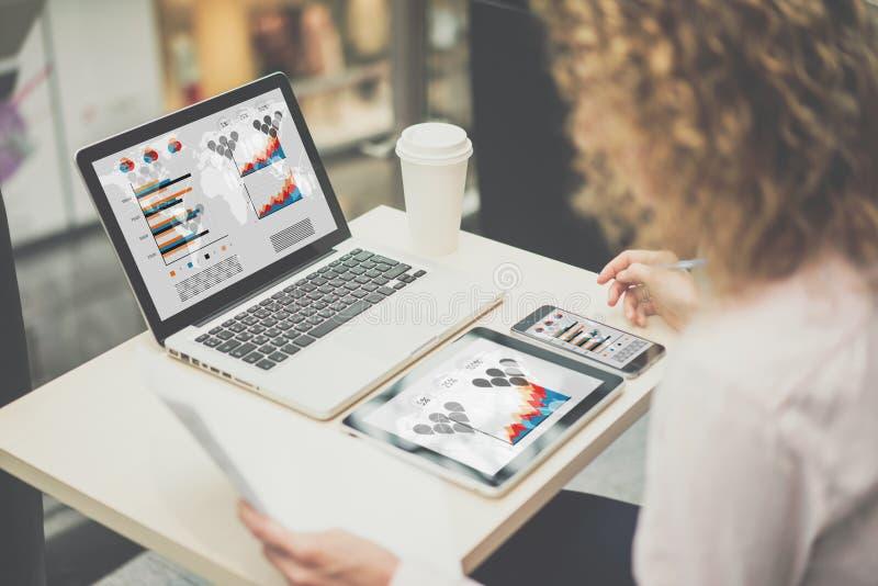 Den bakre sikten, ungt affärskvinnasammanträde på en tabell och arbete, på tabellen är bärbara datorn, minnestavlan, smartphone m arkivbild