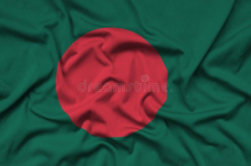 Den Bangladesh flaggan visas på ett sporttorkduketyg med många veck Baner för sportlag arkivbild