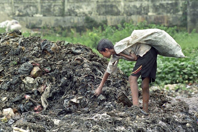 Den bangladeshiska pojken tar användbart gods från nedgrävning av sopor royaltyfria foton