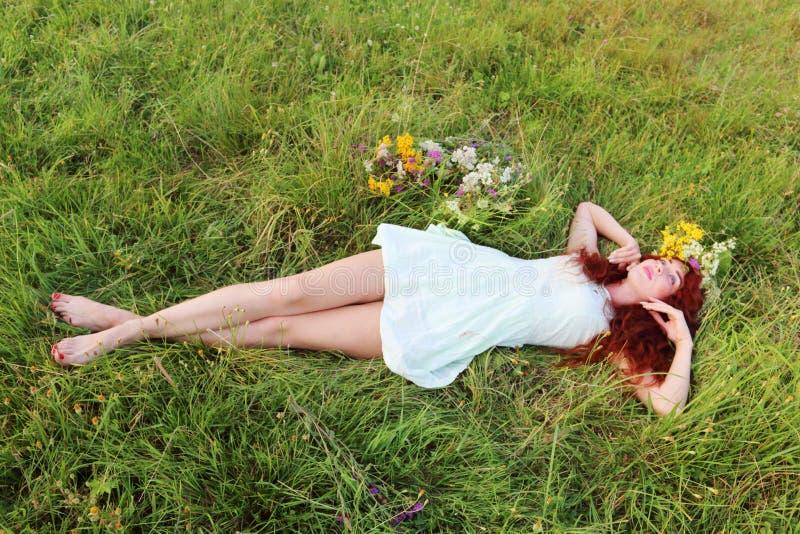 Den barfota flickan i krans ligger på gräs royaltyfri fotografi